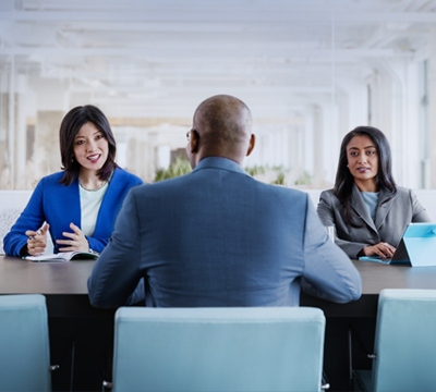 professional man interviewing for a job with two women - Management Interview